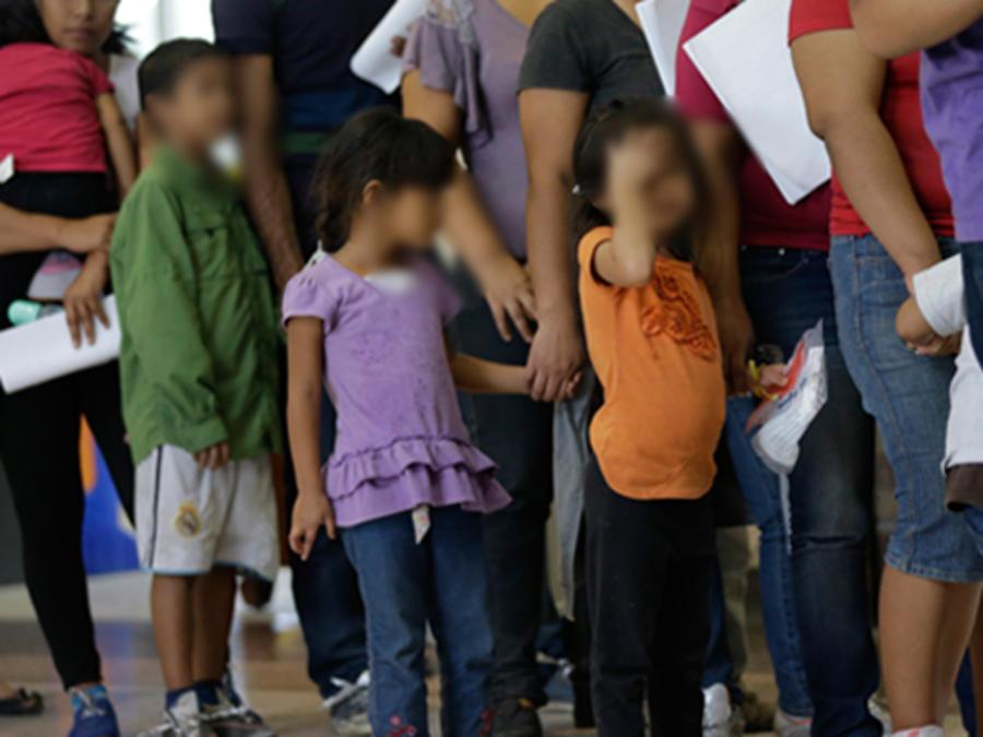 Niños que han cruzado solos la frontera hacen fila junto a adultos a cargo de ellos