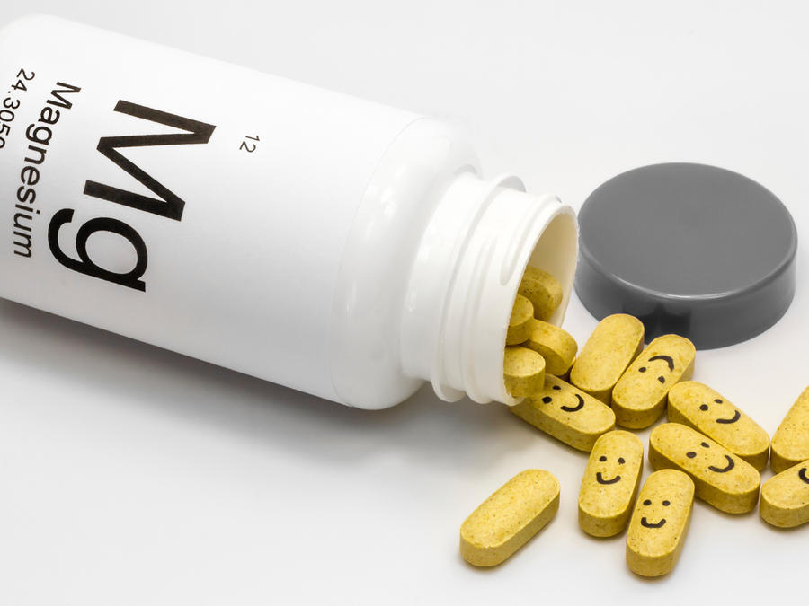 Botella abierta de vitaminas de magnesio