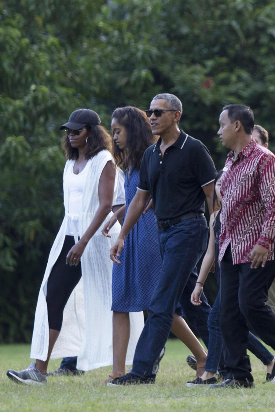 Barack y Michelle Obama paseando con sus hijas