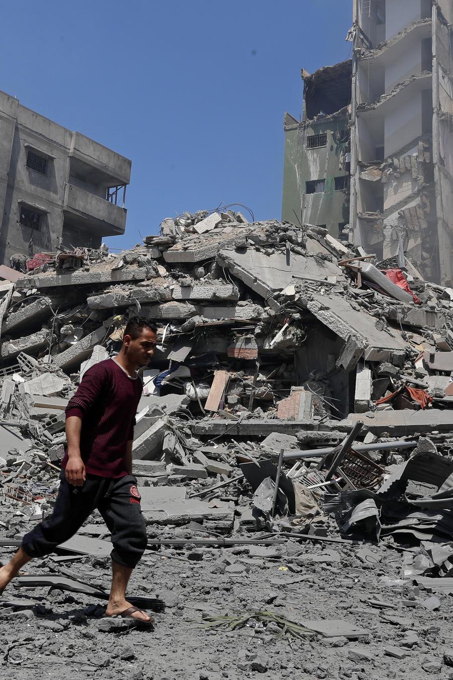 Un hombre camina junto a los escombros del edificio residencial Yazegi, que fue destruido por un ataque aéreo israelí en la ciudad de Gaza, el domingo 16 de mayo de 2021.