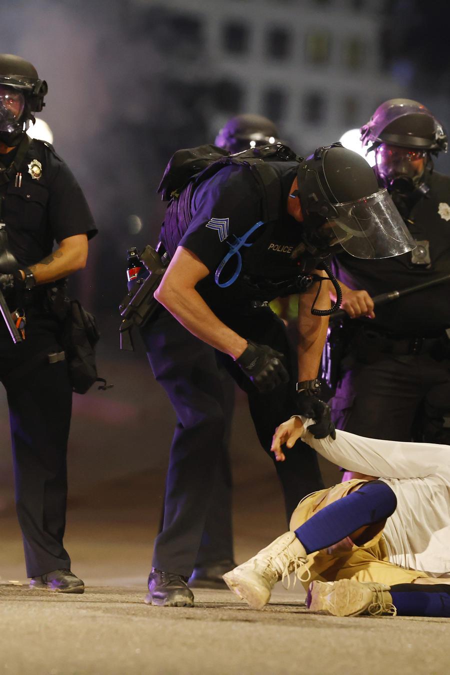 Oficiales del Departamento de Policía de Denver, Colorado,  desalojan a un hombre que cayó en la calle después de que estos usaran gases lacrimógenos y balas de goma para dispersar una protesta frente al Capitolio del estado.