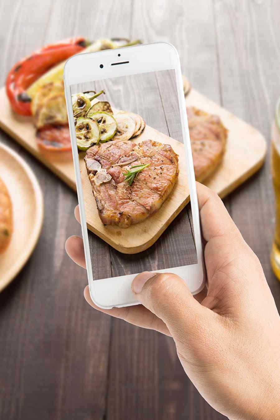 Manos tomando foto a la comida con el celular