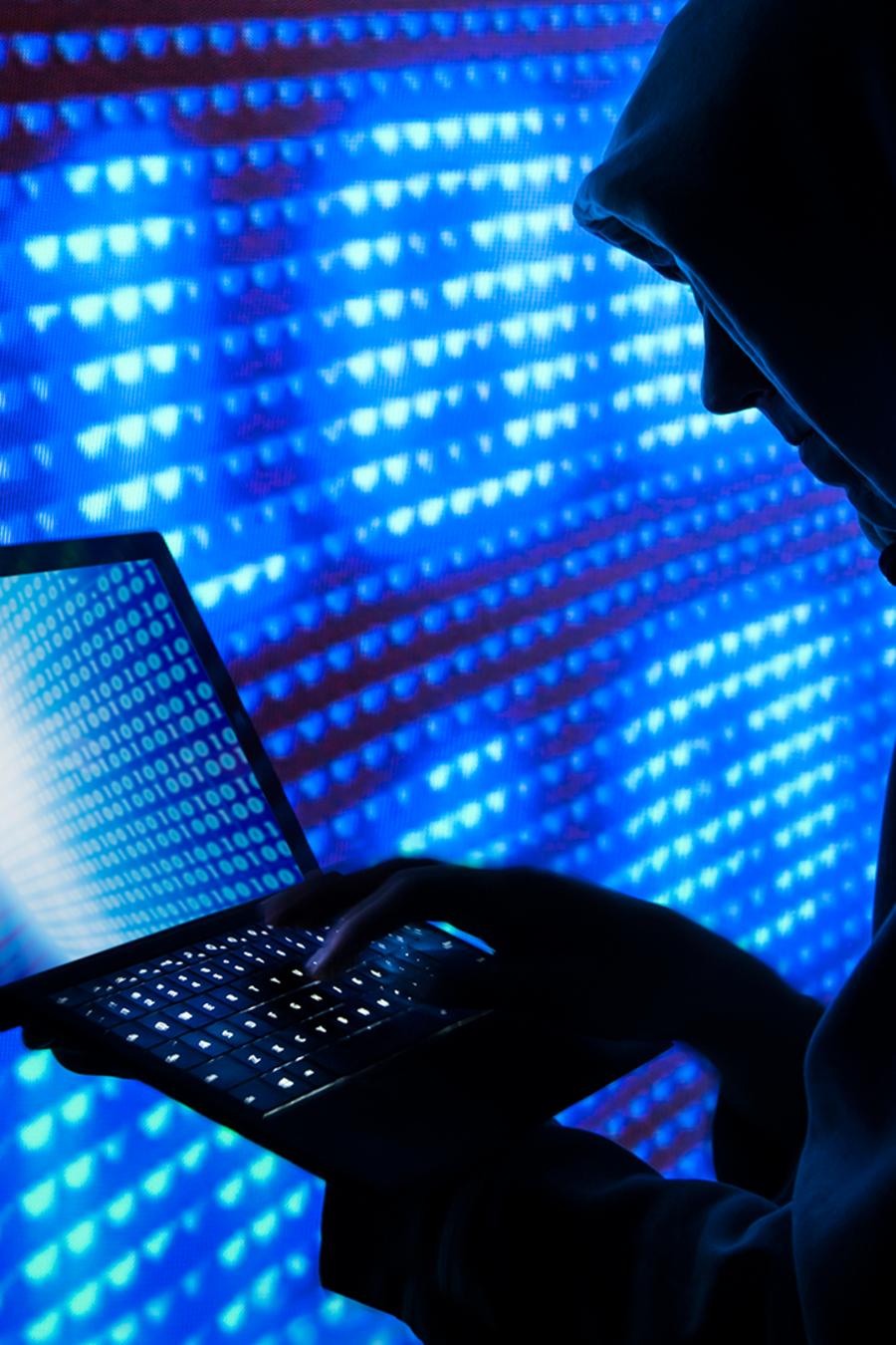 Un supuesto pirata cibernético trabaja en un computador portátil