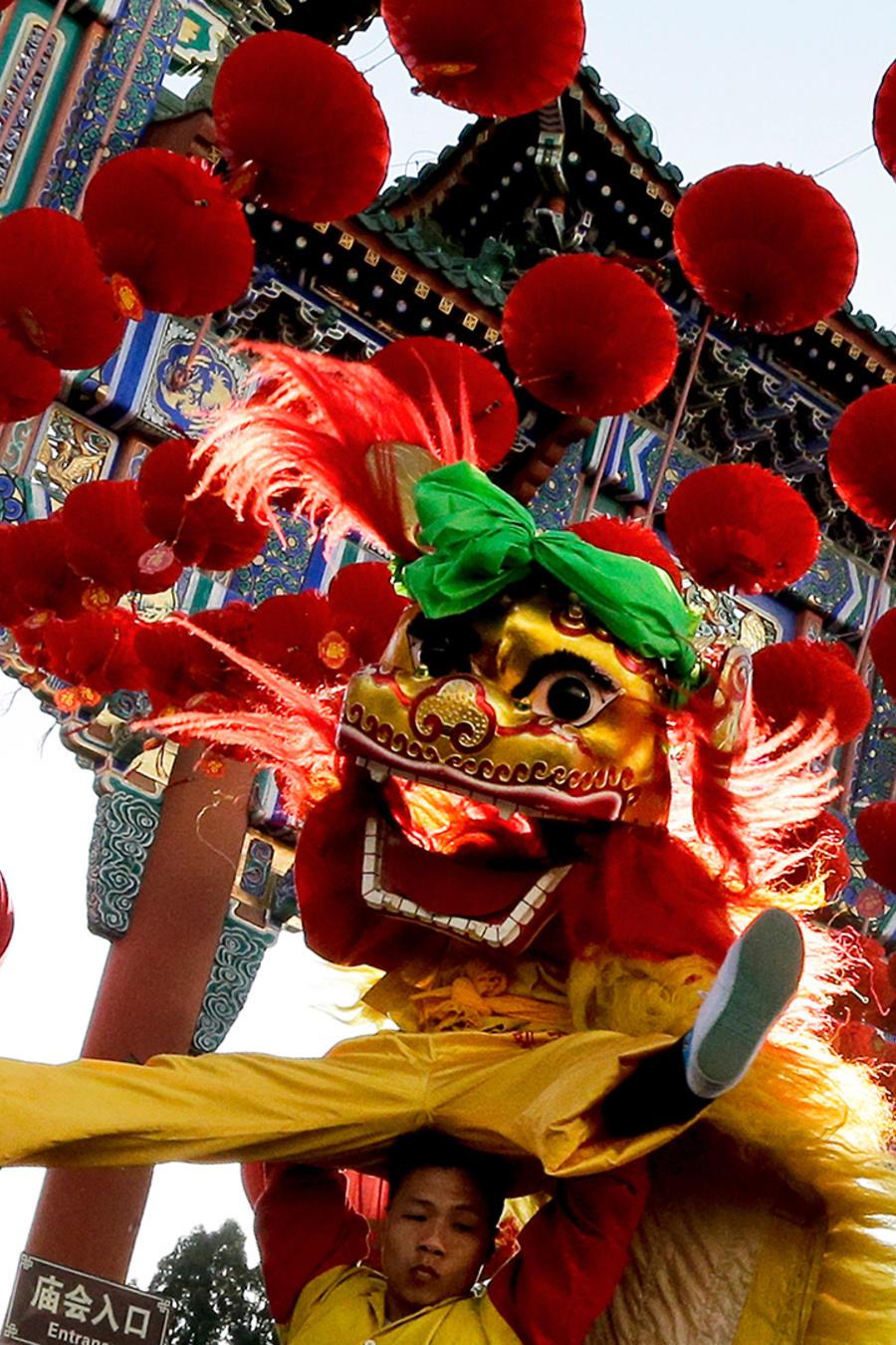 Intérpretes participan en una danza que representa a leones en el parque Ditan en el primer día del Año Nuevo Lunar en Beijing, el lunes 8 de febrero de 2016.