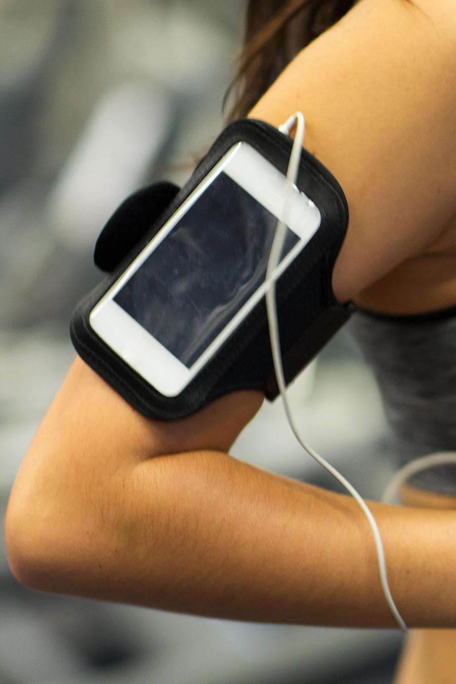 Mujer corriendo con celular en el brazo y auriculares