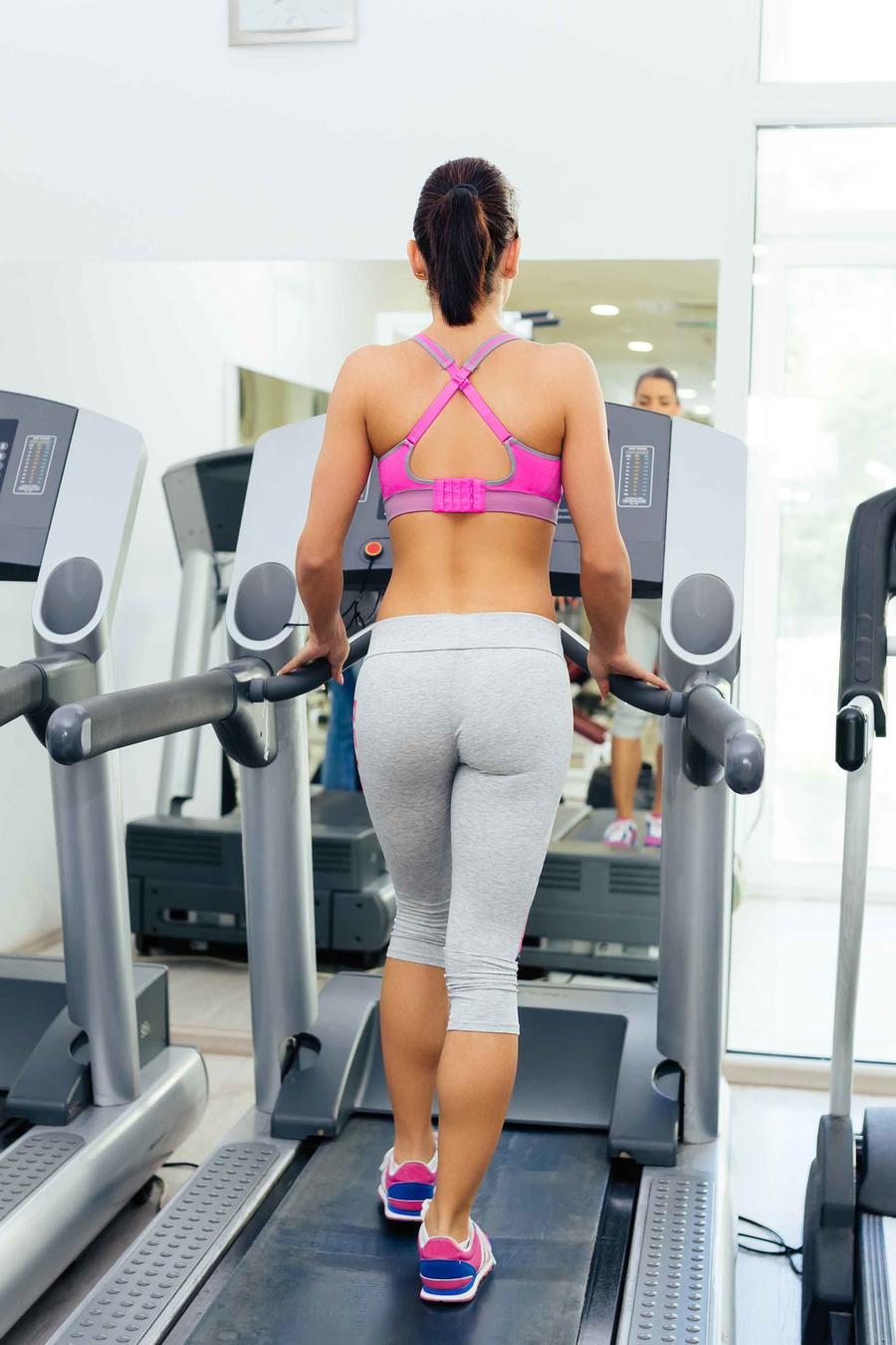 Mujer caminando sobre cinta en gimnasio