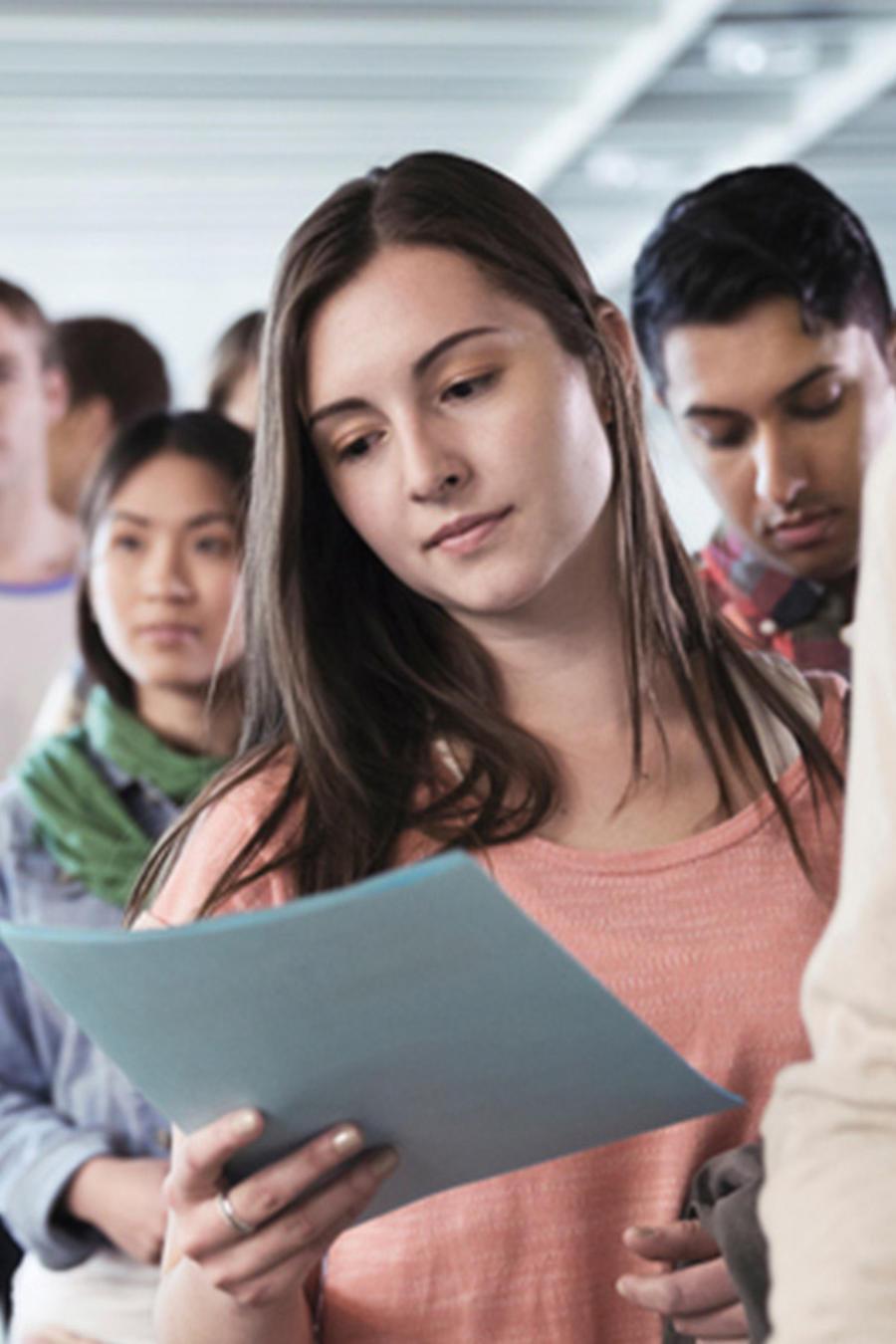 Mujer joven lee en fila un ensayo de admisión