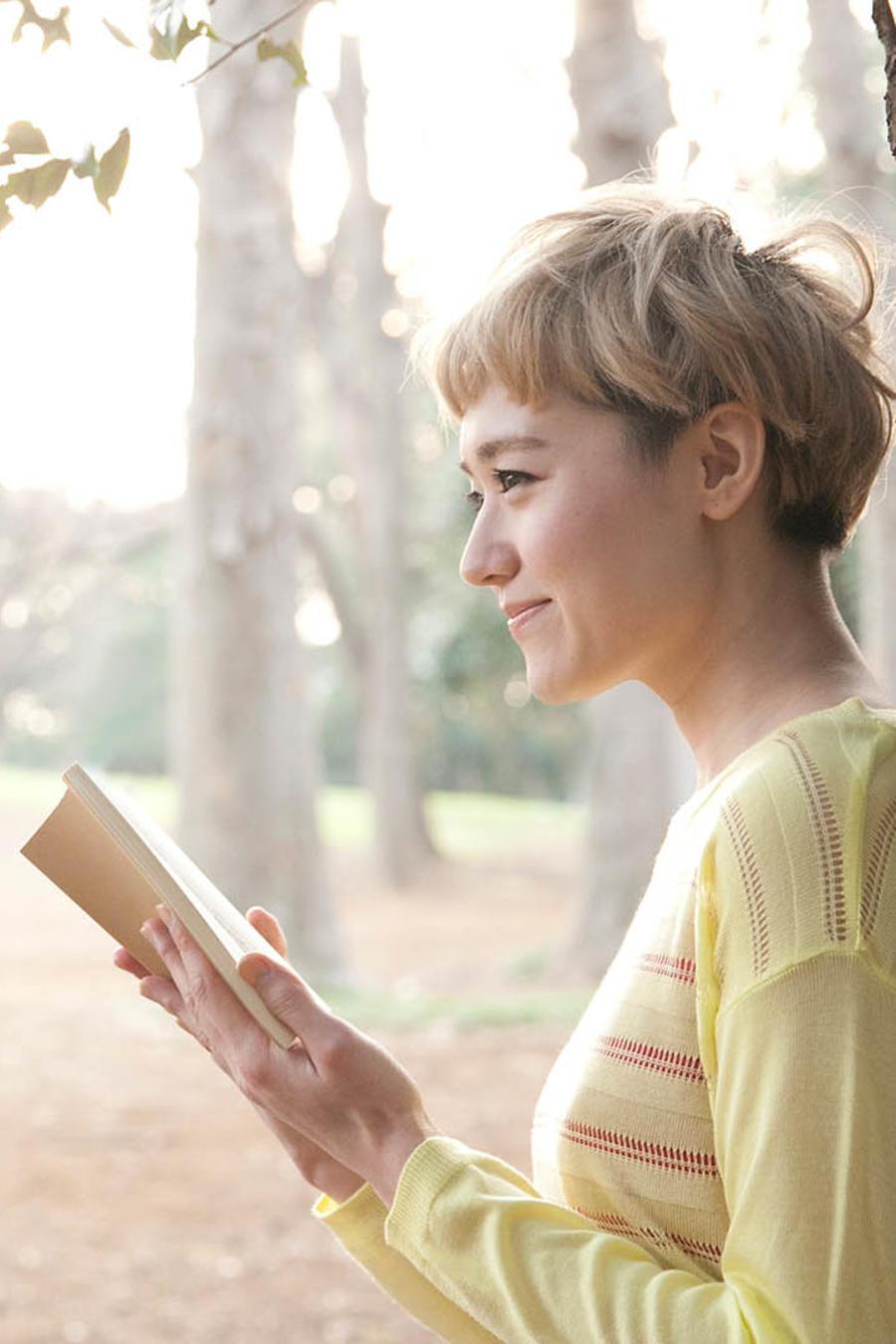 Mujer rubia leyendo junto a un árbol