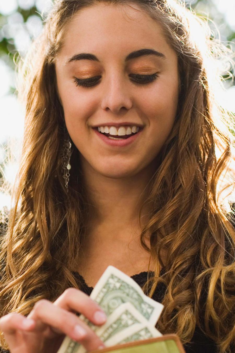 Chica adolescente revisa billetes y sonríe
