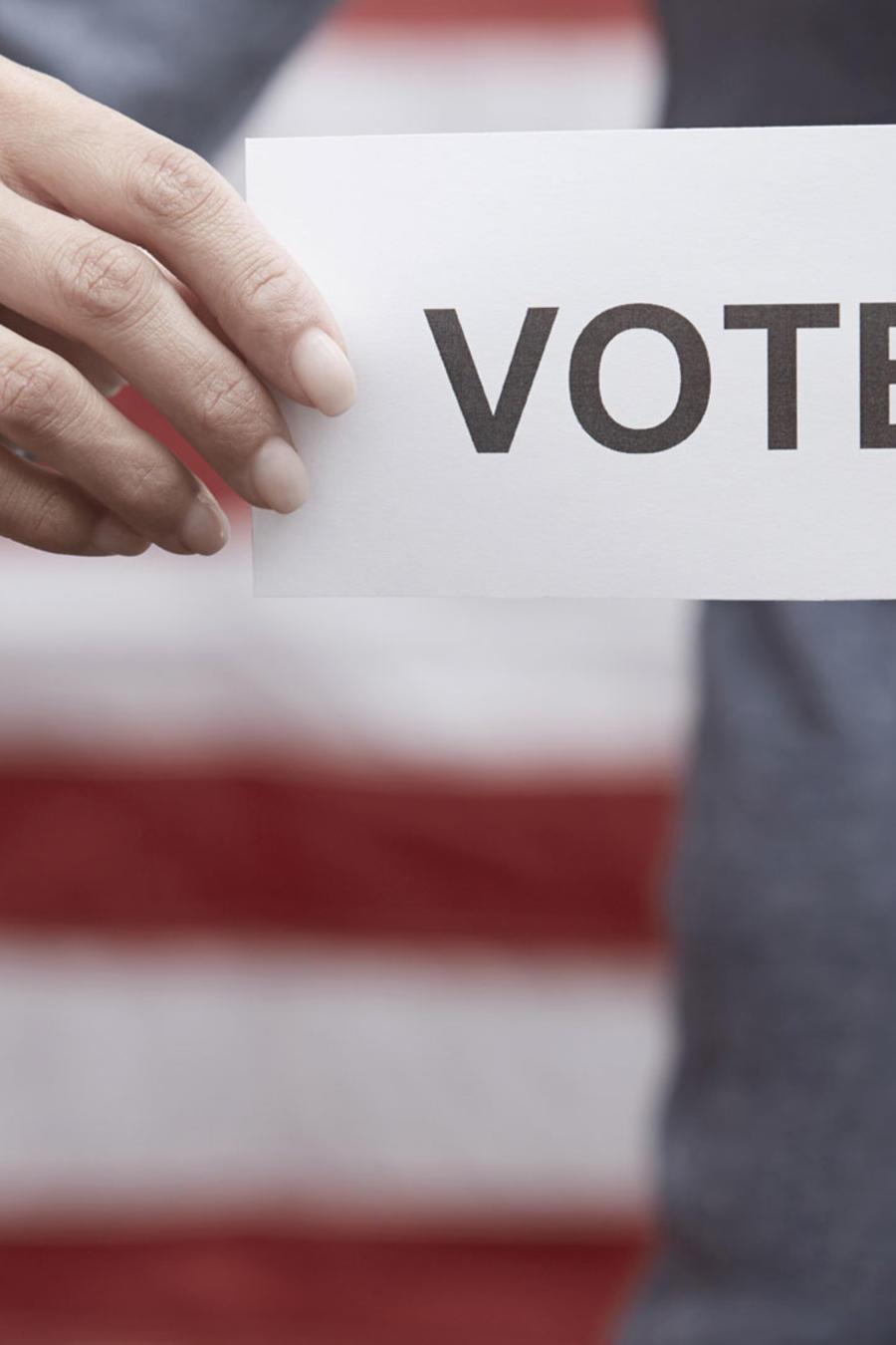 """Mujer sostiene cartel con la palabra """"Vote"""""""
