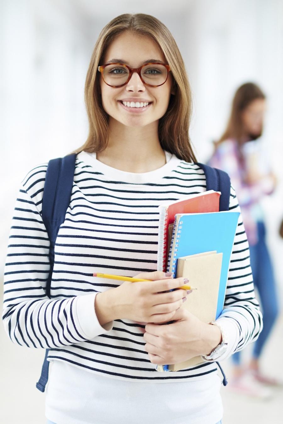 Chica con anteojos cargando libros