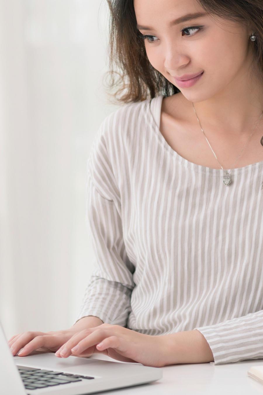 Mujer joven tipea en su laptop