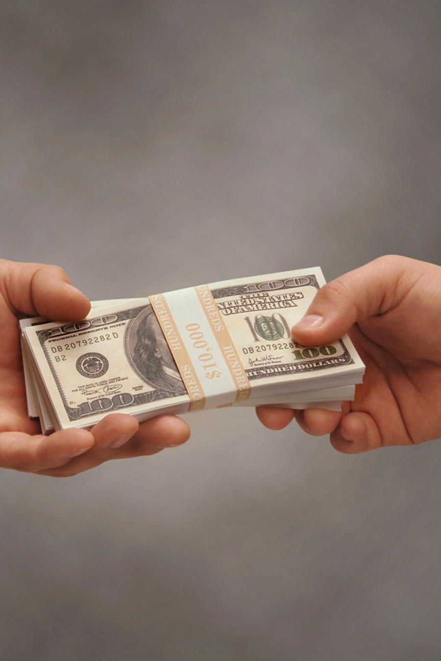 Manos de hombres se pasan dinero