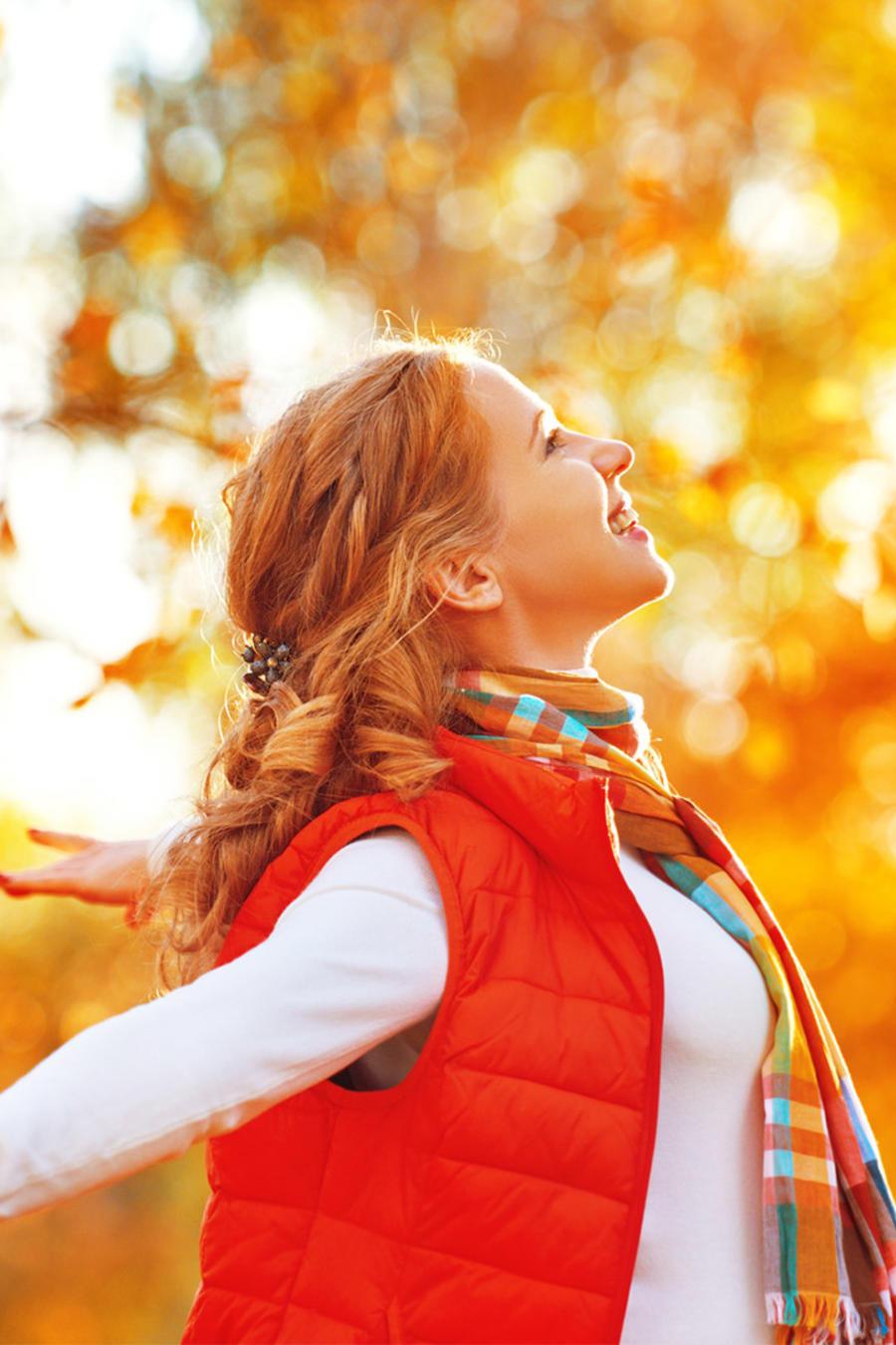 Mujer feliz respira entre árboles de otoño
