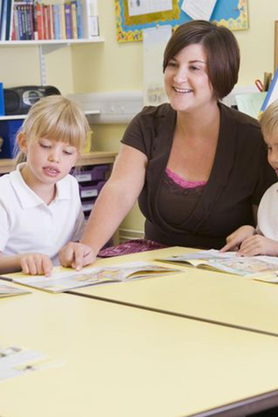 Una maestra se dirige a sus estudiantes en el salón de clases