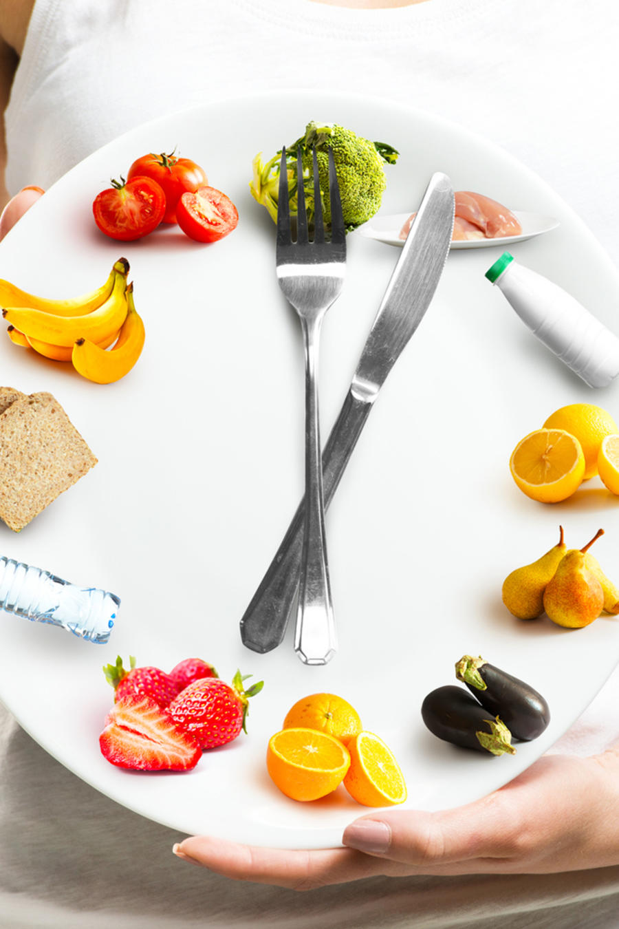 Mujer sosteniendo reloj que marca la hora con comida