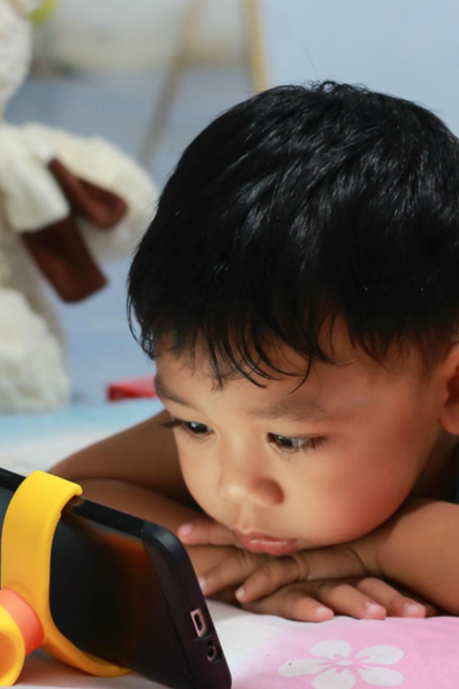 Niño acostado en la cama viendo a la pantalla de un celular