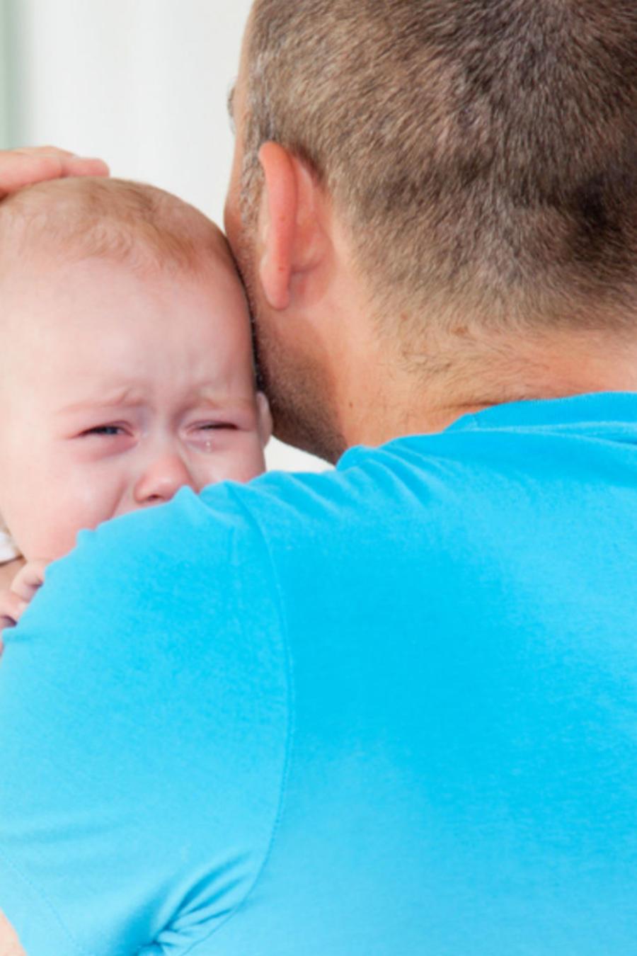 Papá cargando a bebe mientras llora
