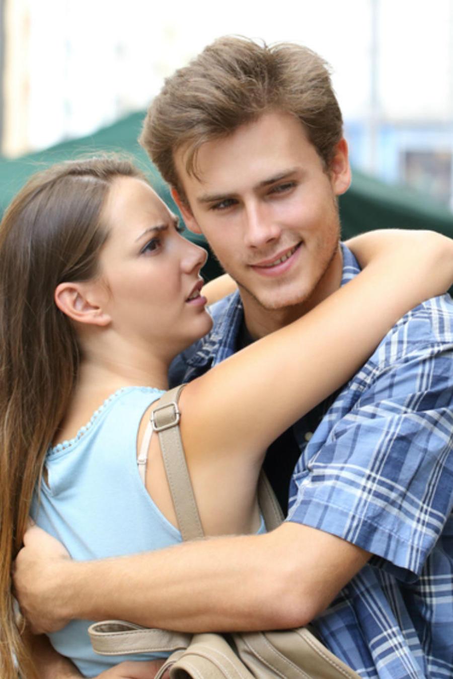 Hombre mirando a una mujer mientras abraza a su novia