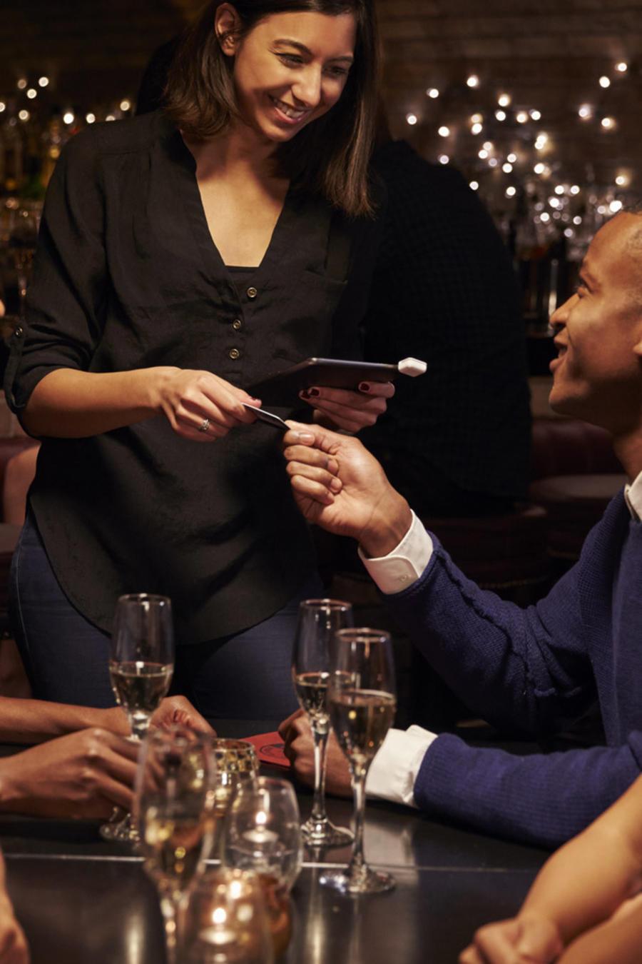 Camarera tomando un pago a un grupo de amigos, en un restaurant