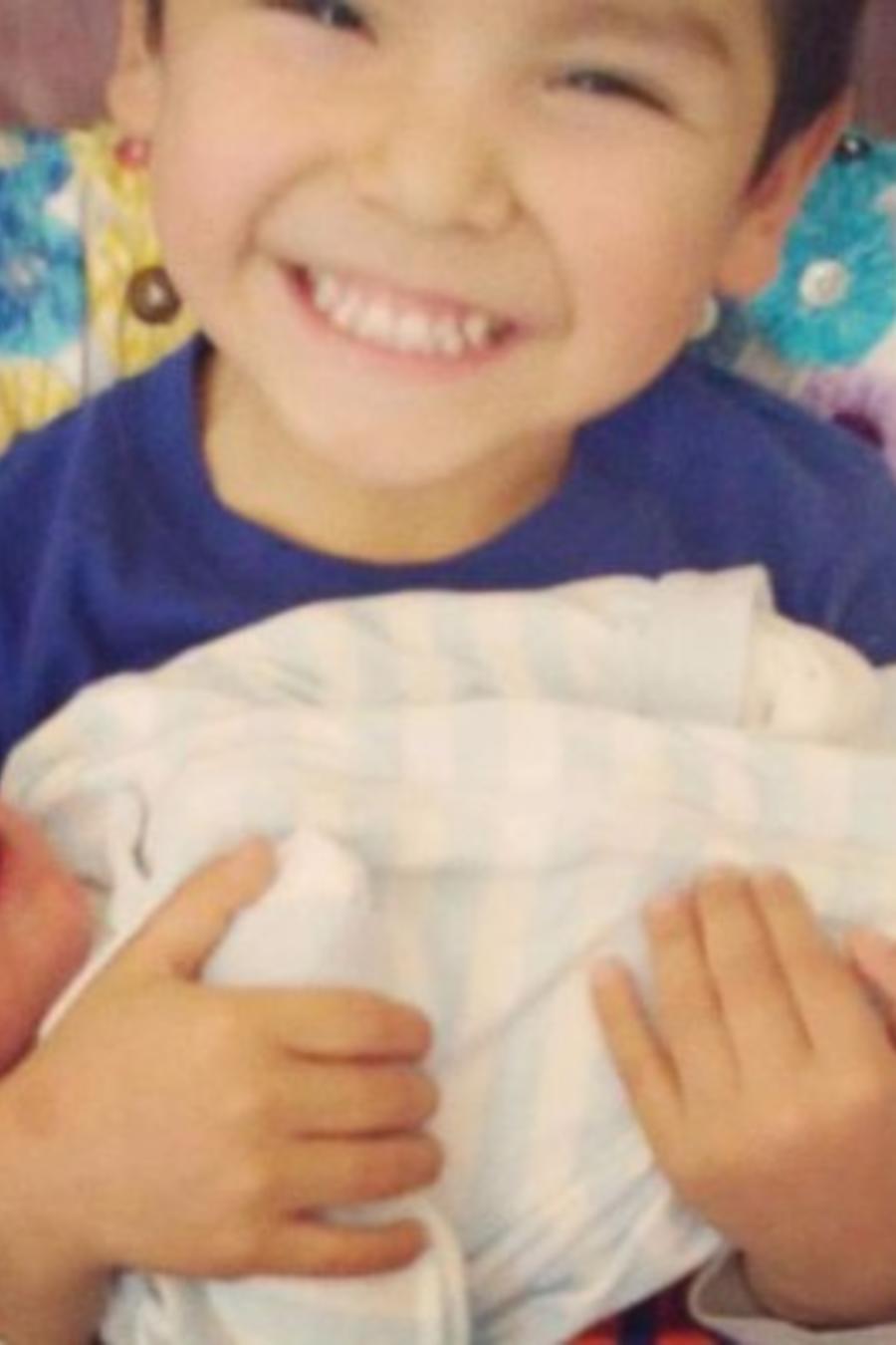 Ryu Pena, el niño fallecido, con su hermanito en brazos
