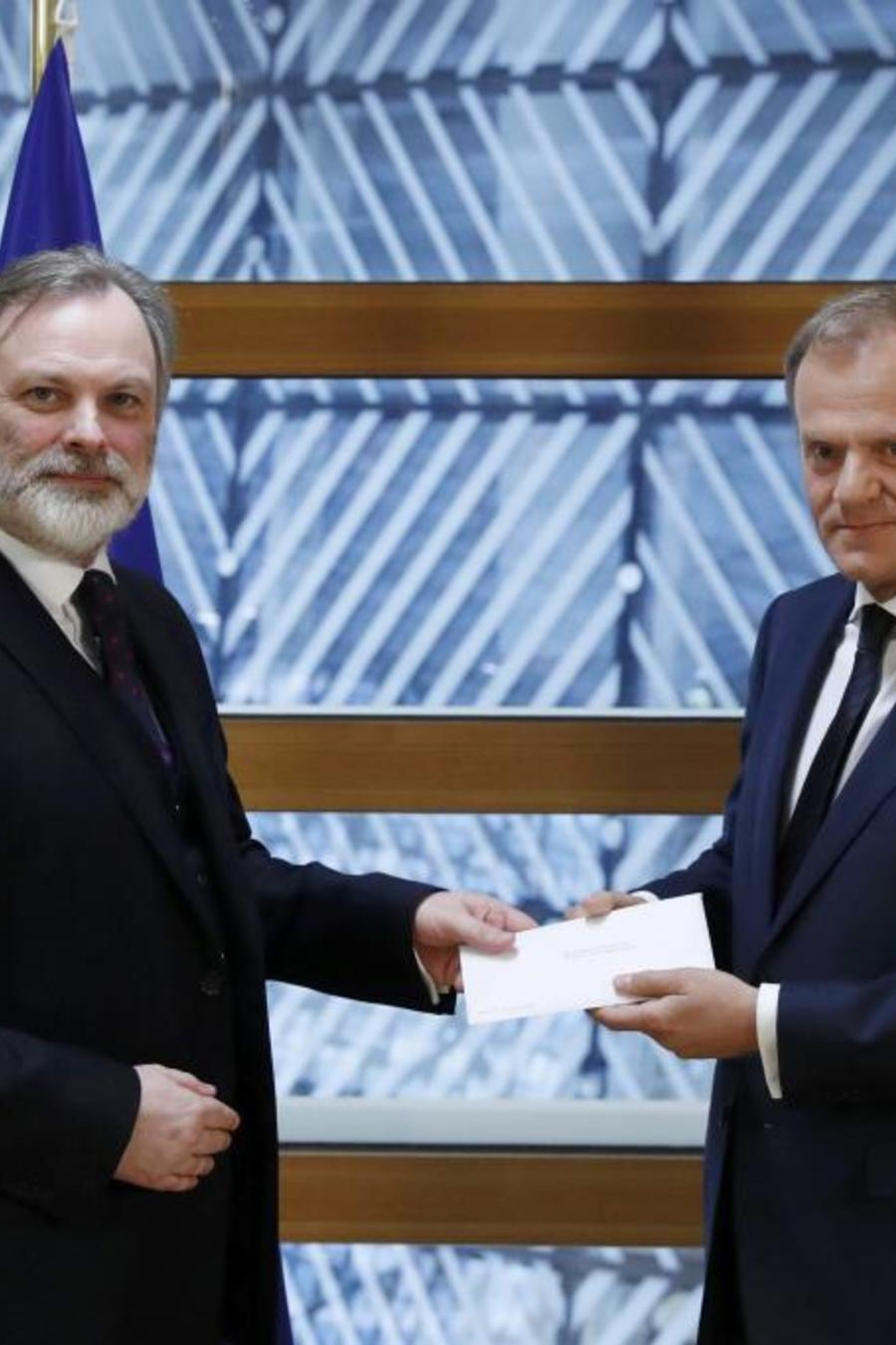 Britain's permanent representative to the European Union Tim Barrow delivers British Prime Minister Theresa May's Brexit letter to EU Council President Donald Tusk in Brussels
