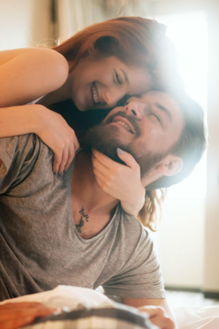 Mujer abrazando a un hombre y sonriendo en la cama