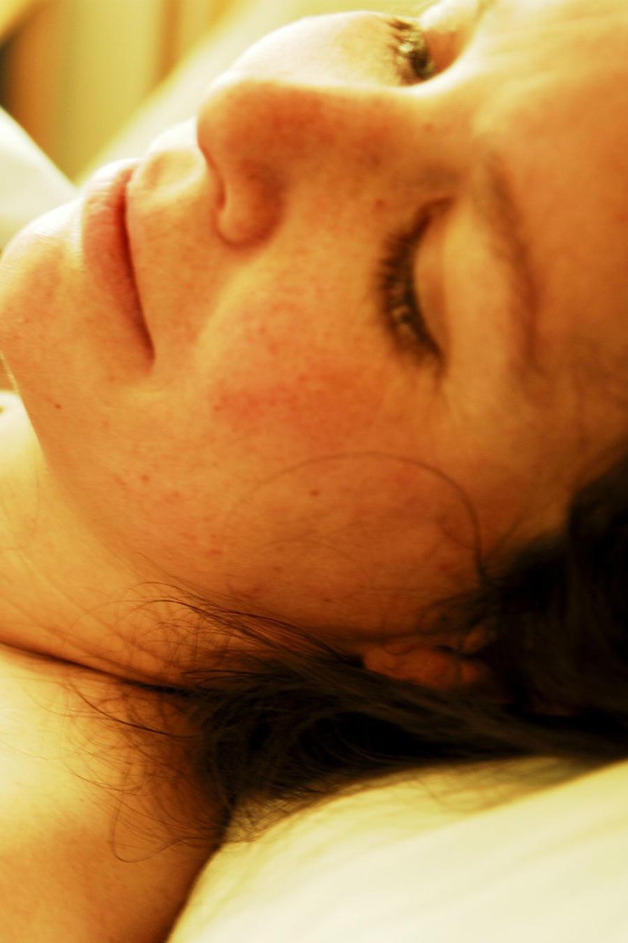 Mujer en la cama de un hospital con un recién nacido en brazos