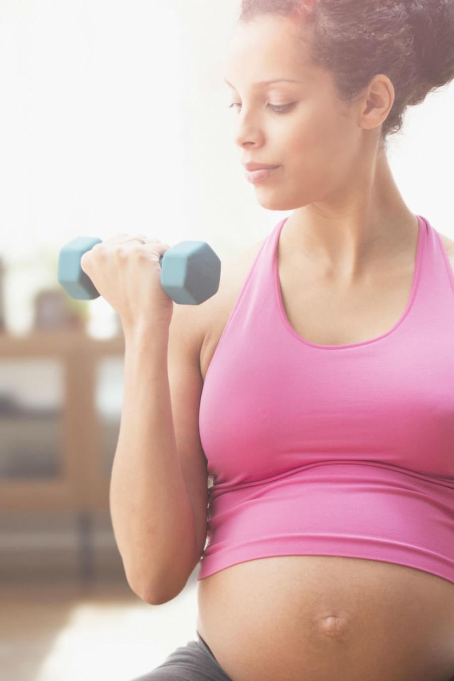 Mujer embarazada haciendo ejercicio con pesas