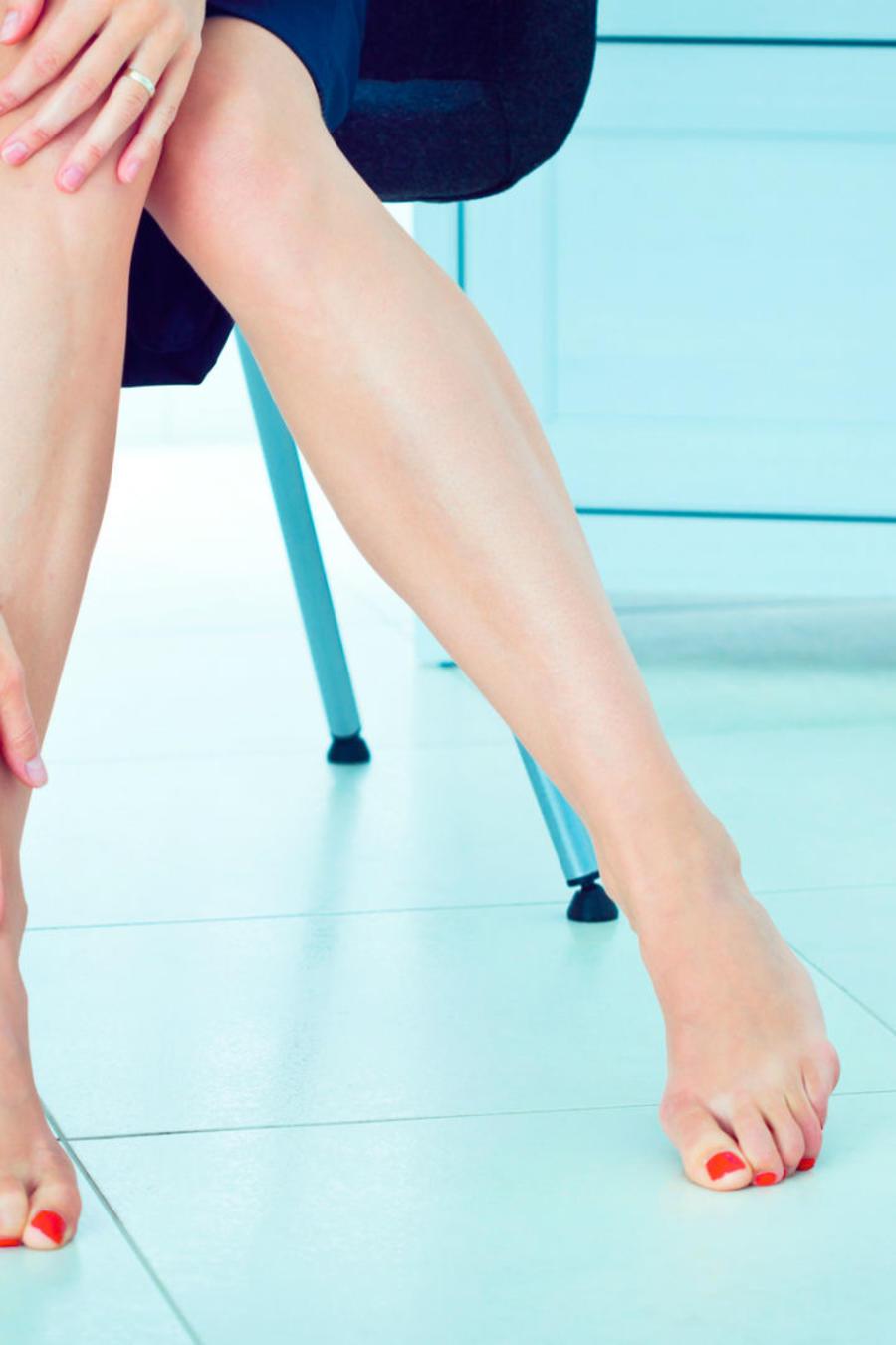 Piernas de una mujer con los zapatos al lado