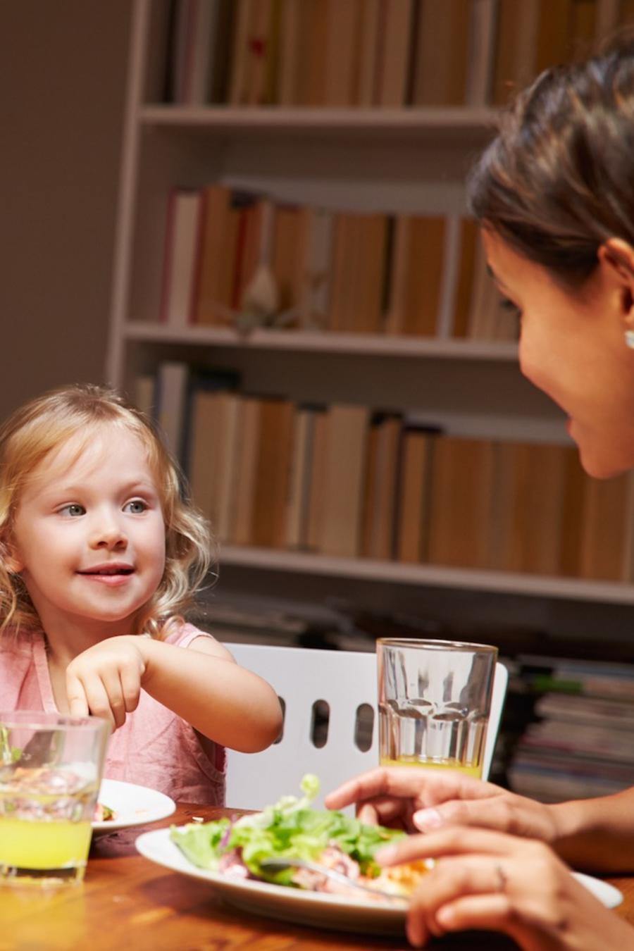 Padres e hija comiendo en la mesa