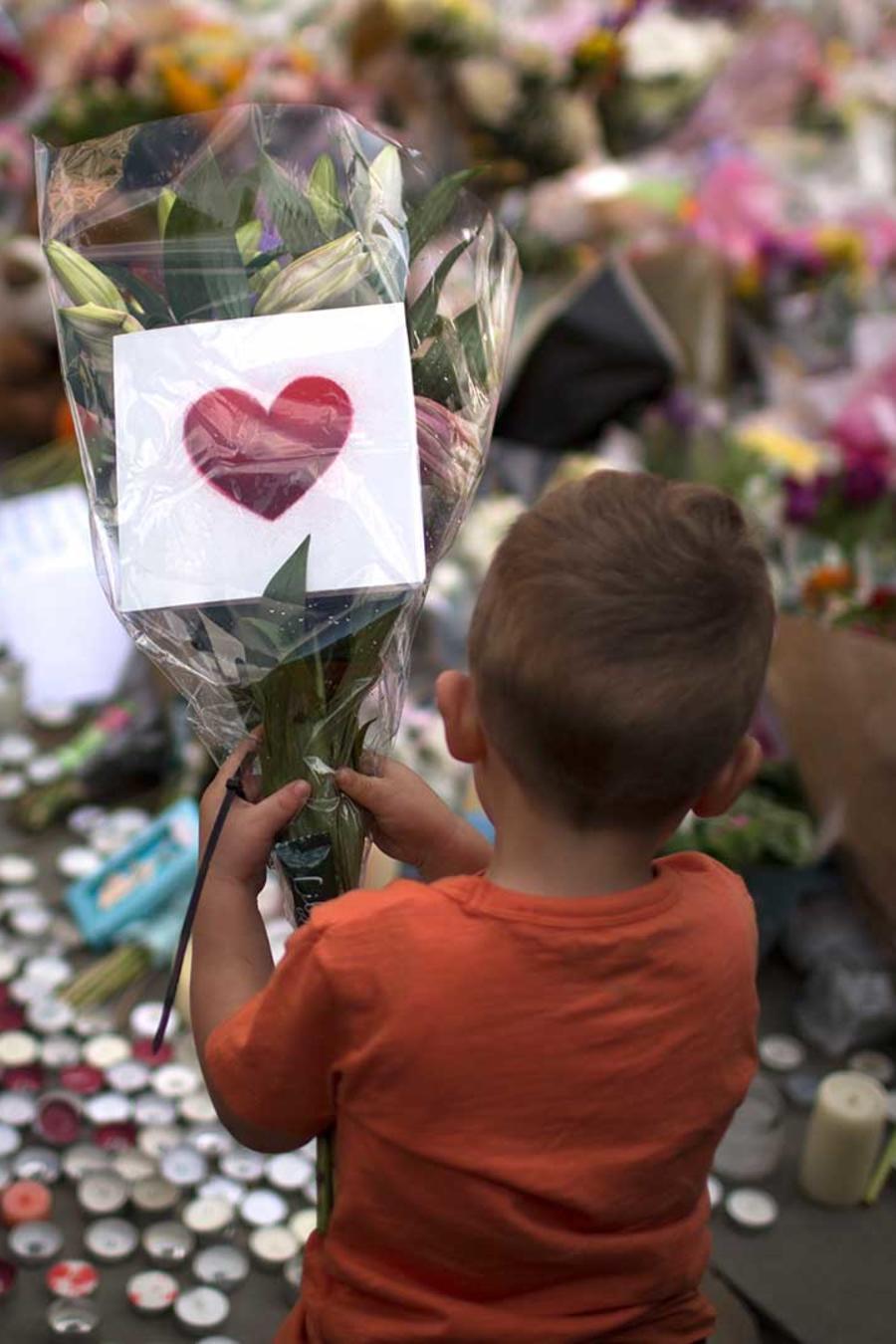 Un niño deja flores por las víctimas del ataque suicida ocurrido después de un concierto de Ariana Grande en Manchester