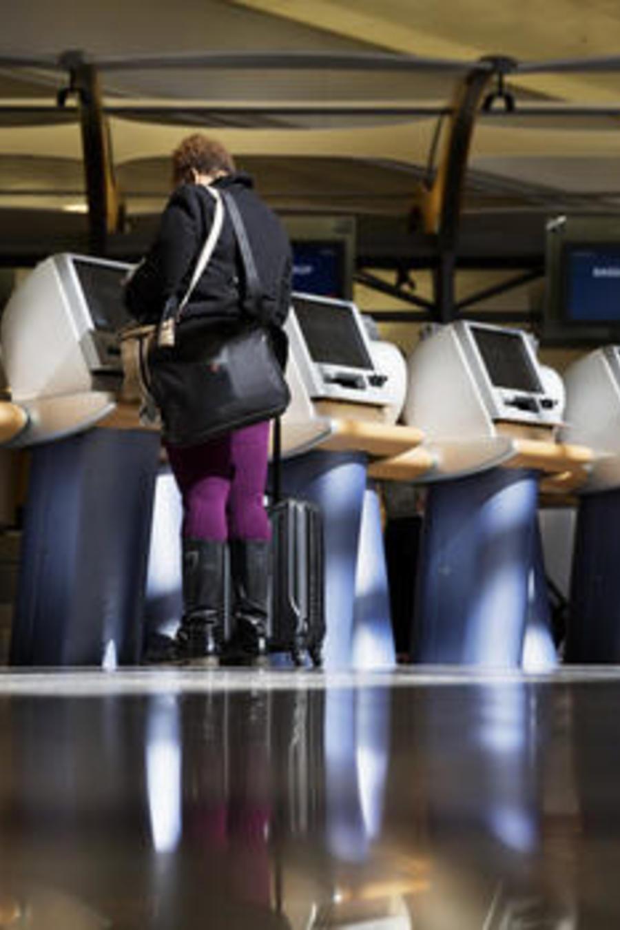 Varios pasajeros tramitan sus pases de abordar en quioscos de Delta Airlines en el aeropuerto Internacional de Atlanta.