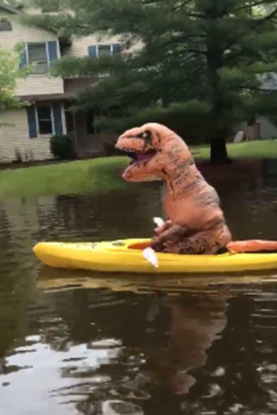 Una persona disfrazada de dinosaurio se pasea en kayak por las inundaciones causadas por el mal tiempo en Midland, Michigan
