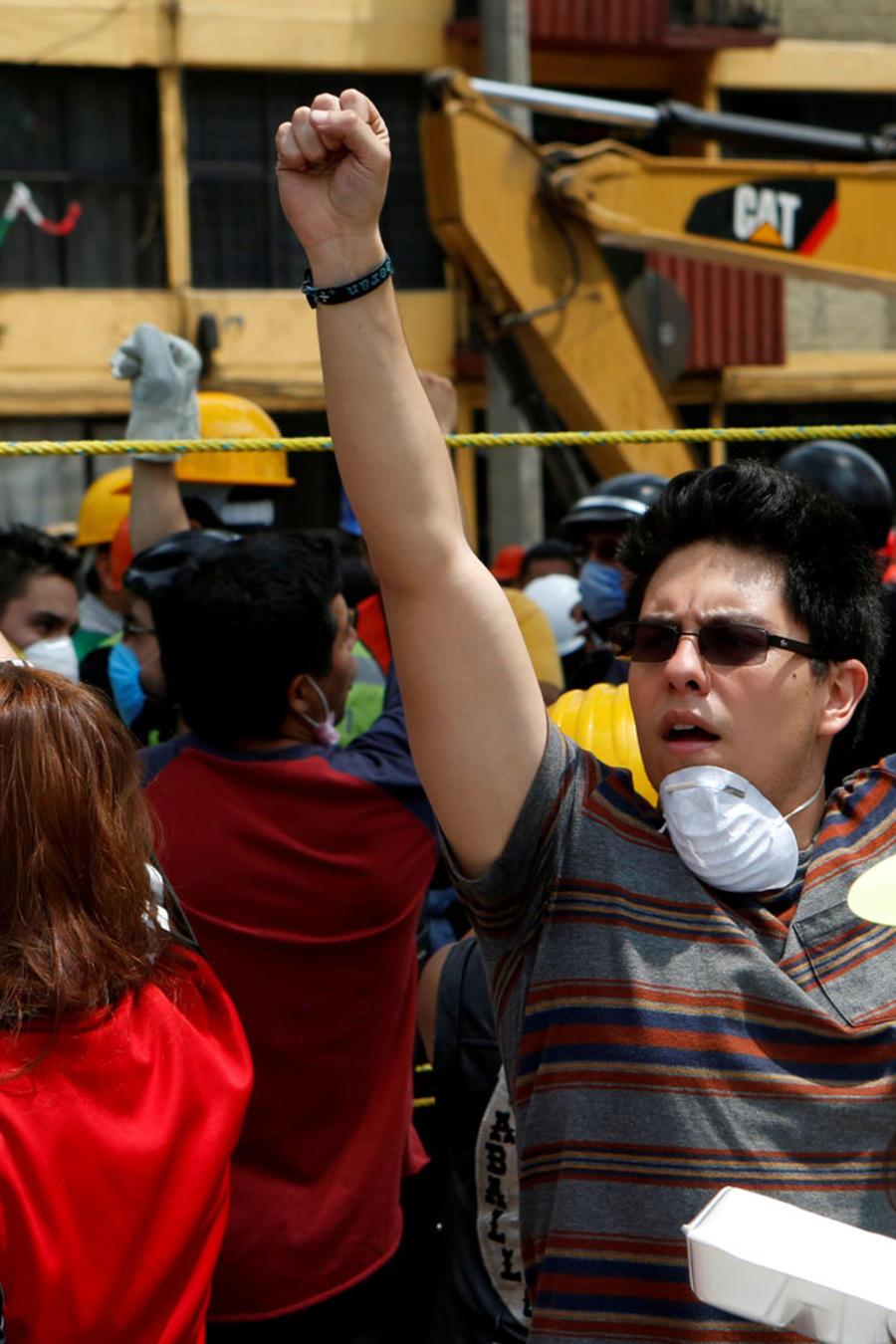 Varias personas levantan sus puños en medio de labores de rescate en la Ciudad de México, el 20 de septiembre de 2017