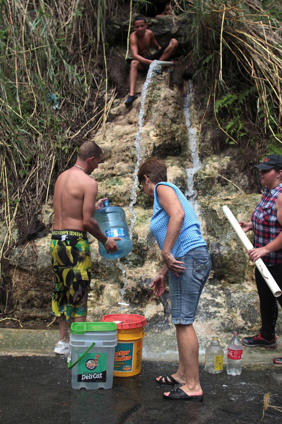 En esta foto del 17 de octubre de 2017, varias personas recogen agua de un manantial de montaña en la Corozal, Puerto Rico.