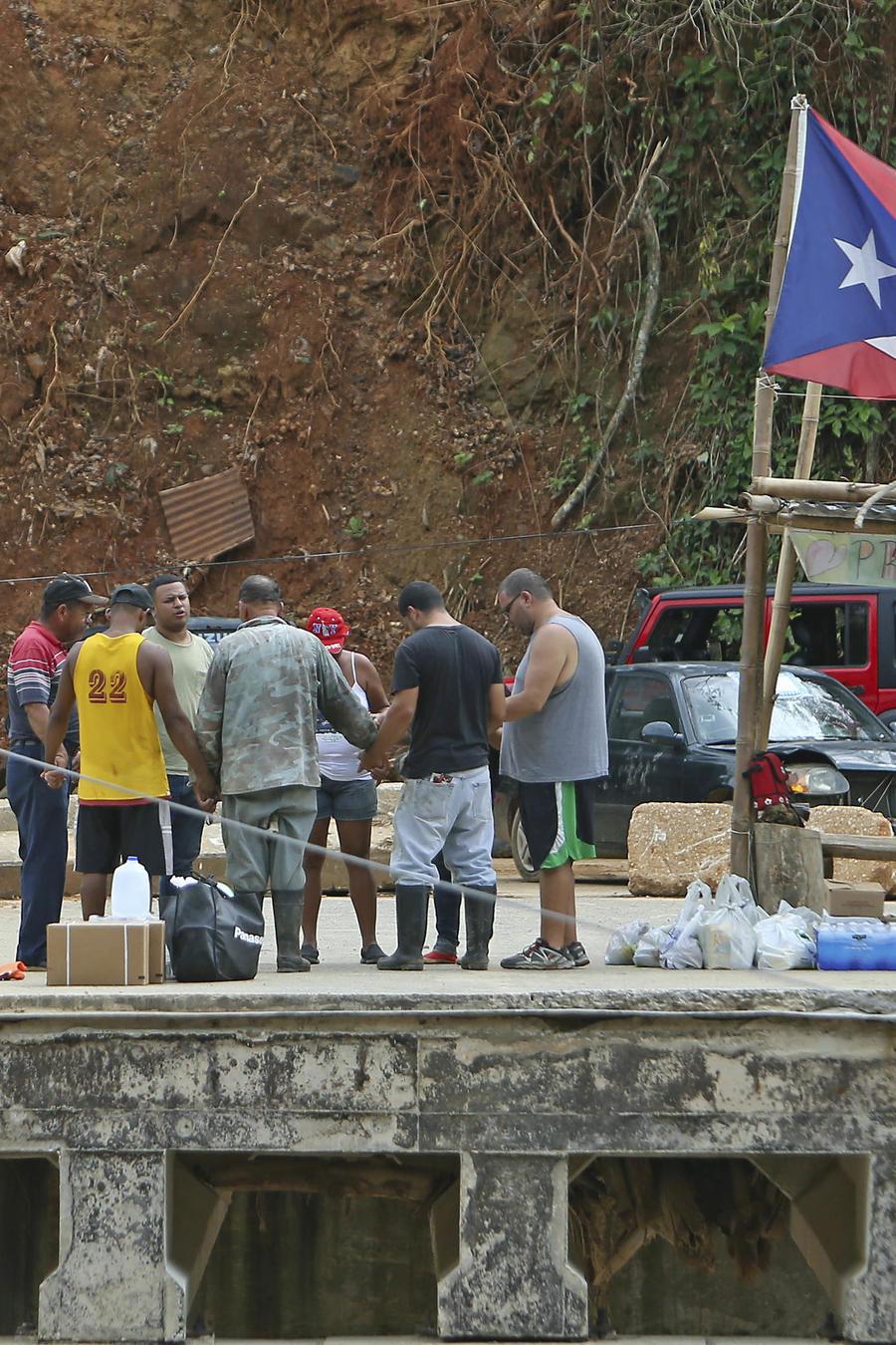 Unas personas rezan en la localidad de Río Abajo, Puerto Rico, mientras siguen los trabajos de recuperación en la isla tras el paso del huracán María.
