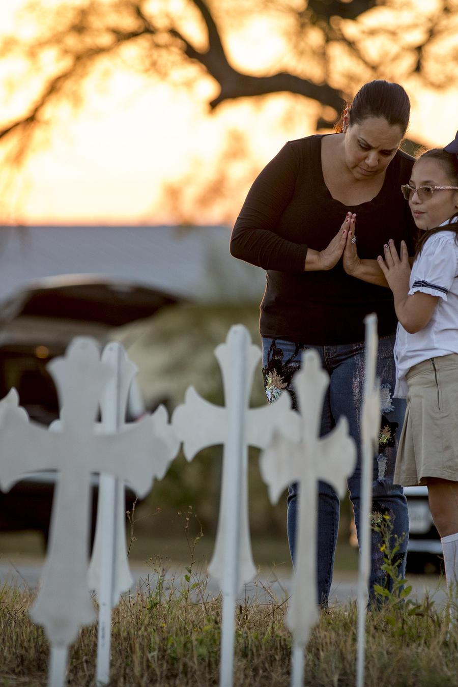 Vecinos visitan un lugar de recuerdo creado con 26 cruces de metal cerca de la Primera Iglesia Bautista de Sutherland Springs.
