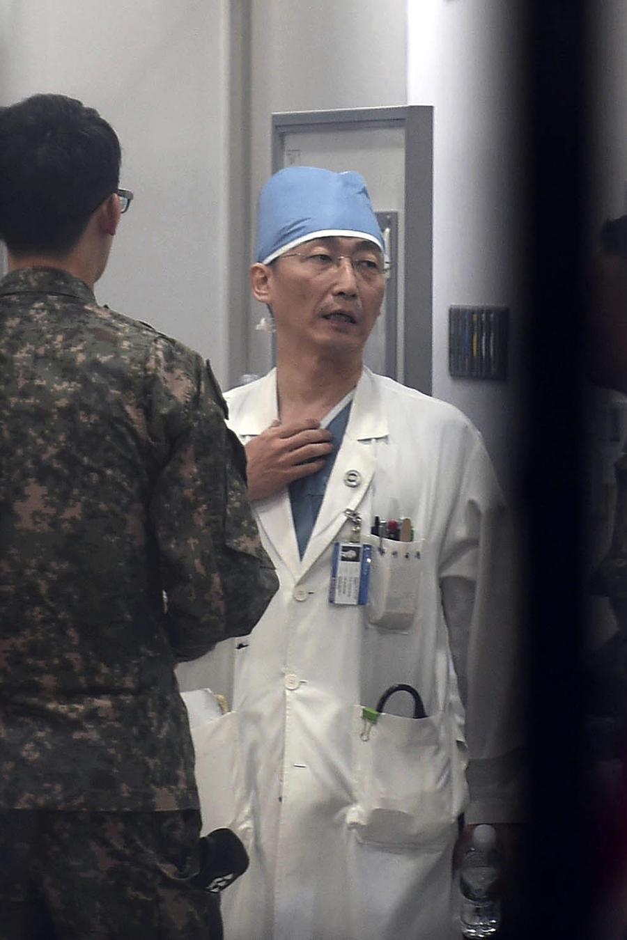 Soldados del ejército surcoreano hablan con un médico mientras se prepara para tratar a una persona no identificada, no vista, que se cree es un soldado norcoreano, en un hospital en Suwon, Corea del Sur, el lunes 13 de noviembre de 2017. Soldados norcore