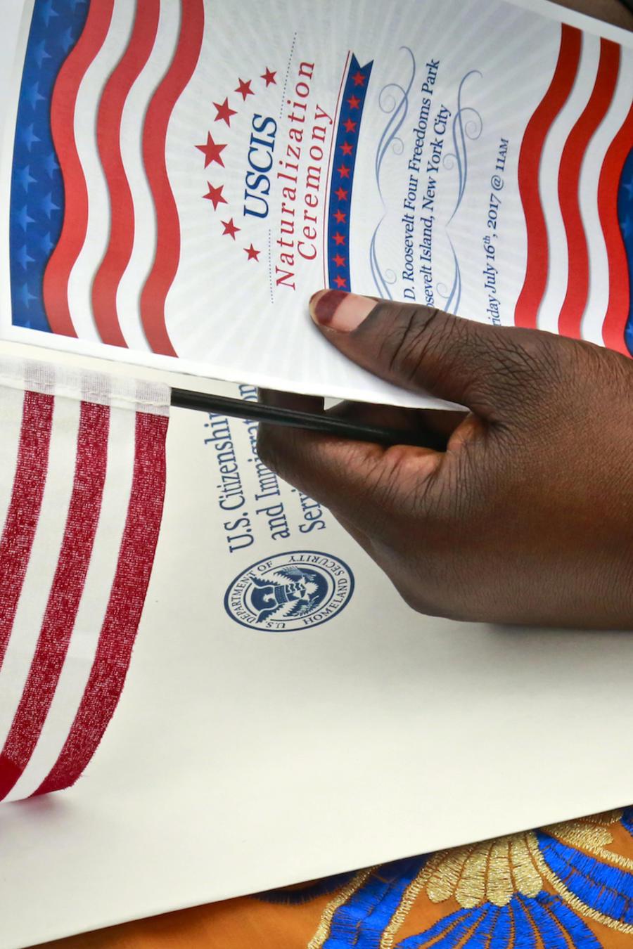 Una inmigrante sostiene una bandera e información de USCIS durante una ceremonia de naturalización en junio en Nueva York.