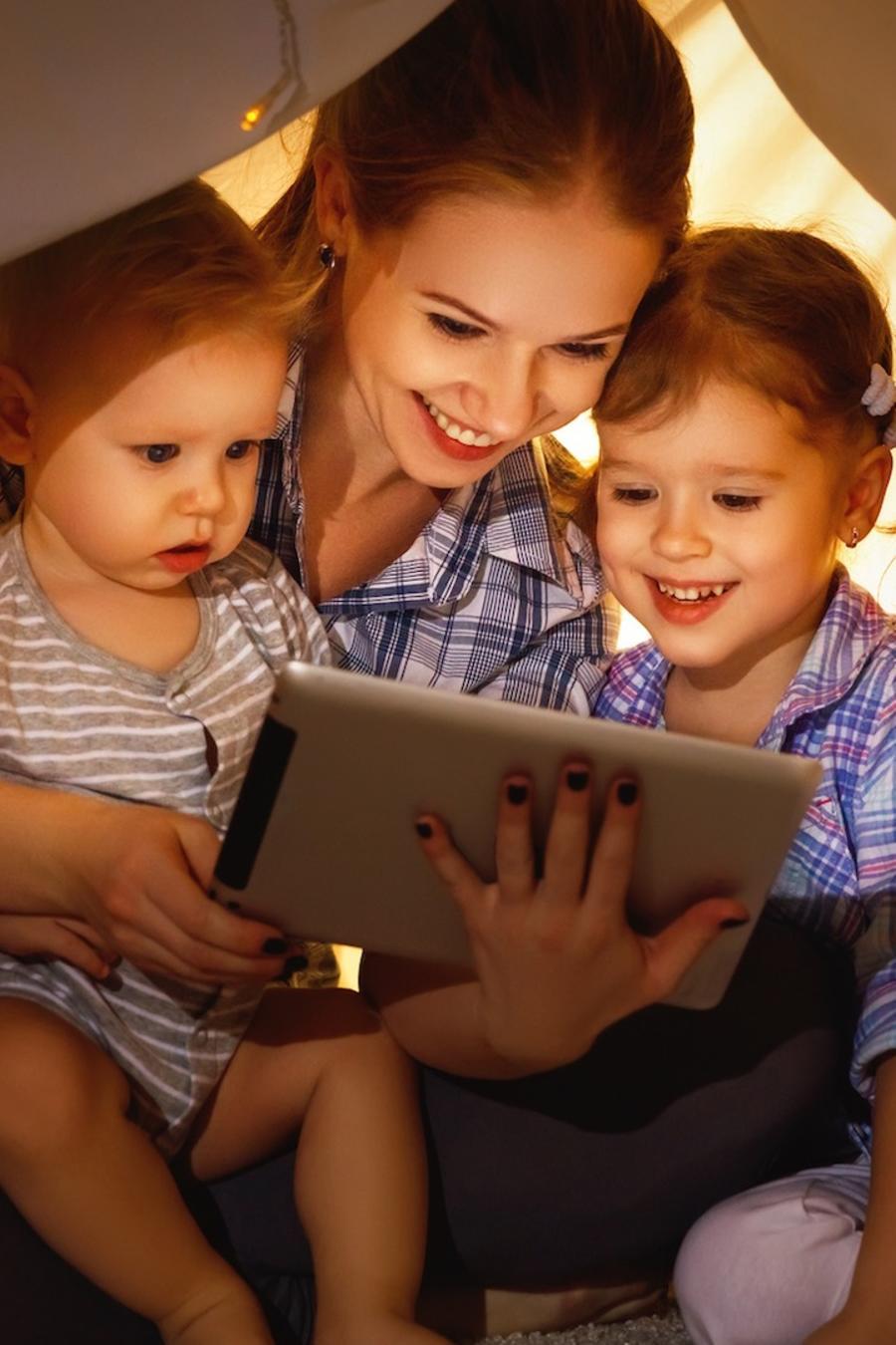 Madre e hijos mirando película en tableta