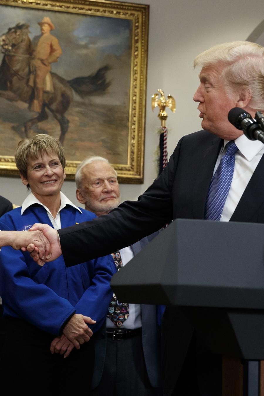 El presidente Donald Trump le da la mano al ex astronauta del Apollo 17 Jack Schmitt antes de firmar una directiva política para enviar de regreso a la luna a los astronautas estadounidenses, y finalmente a Marte, en la Sala Roosevelt de la Casa Blanca.
