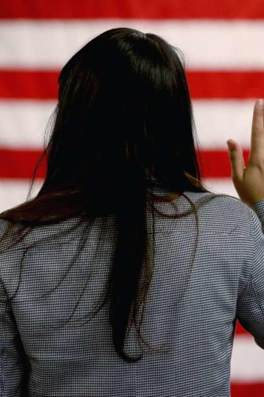 Una mujer jurando ante la bandera de EEUU
