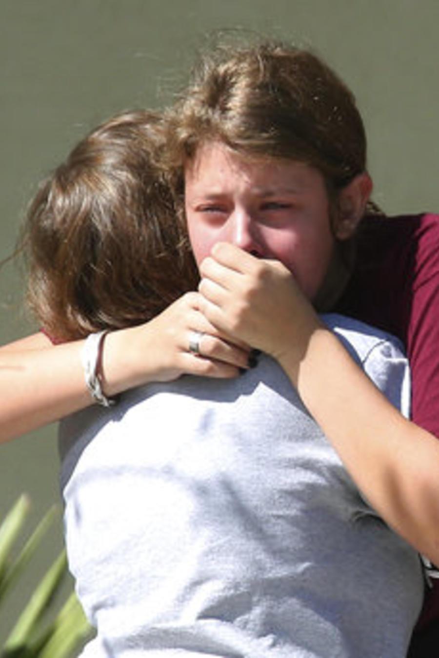 Estudiantes se abrazan tras el terrible tiroteo registrado en el centro Marjory Stoneman Douglas en Parkland, Florida.