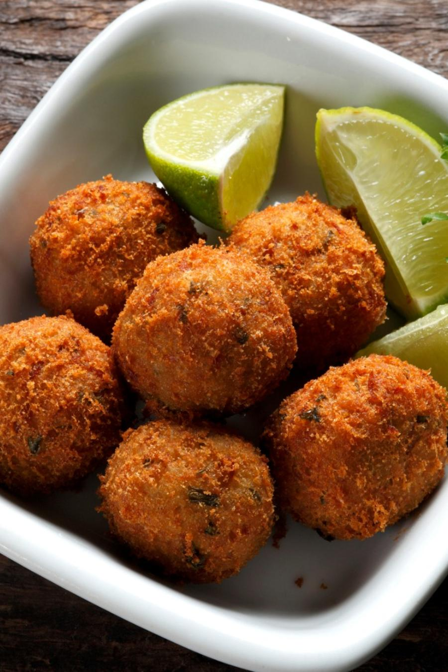 Croquetas with lime on a plate.