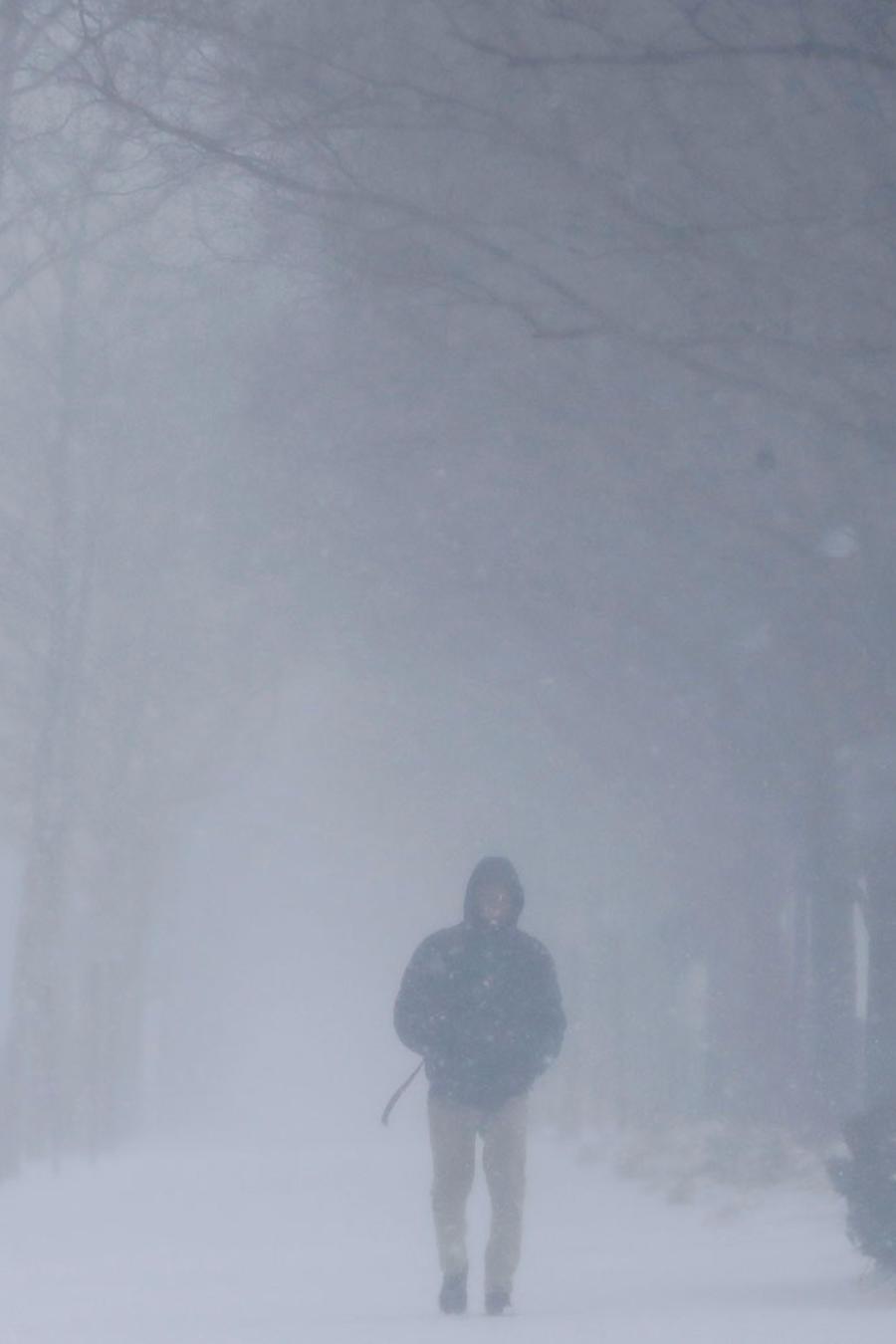 Un hombre camina bajo una capa de nieve durante las primeras etapas de una tormenta de nieve, el miércoles 21 de marzo de 2018 en Hoboken, N.J. (Foto AP / Julio Cortez)