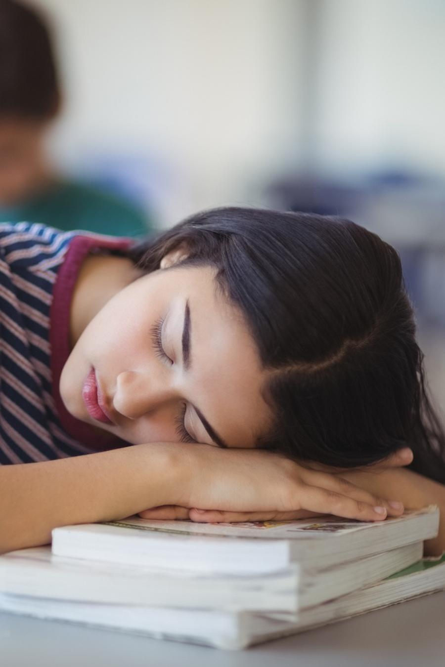Joven adolescente durmiendo sobre sus libros
