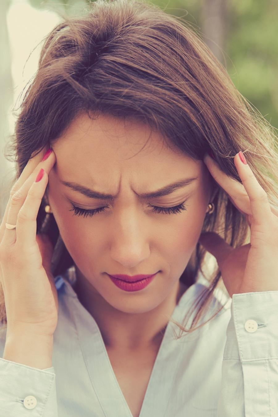 Mujer tomándose la cabeza con ambas manos