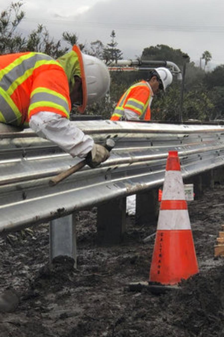 Varios trabajadores trabajan en una seccion dañada de la US 101 en Montecito, California, cubierta por lodo de las inundaciones registradasa a principios de 2018.