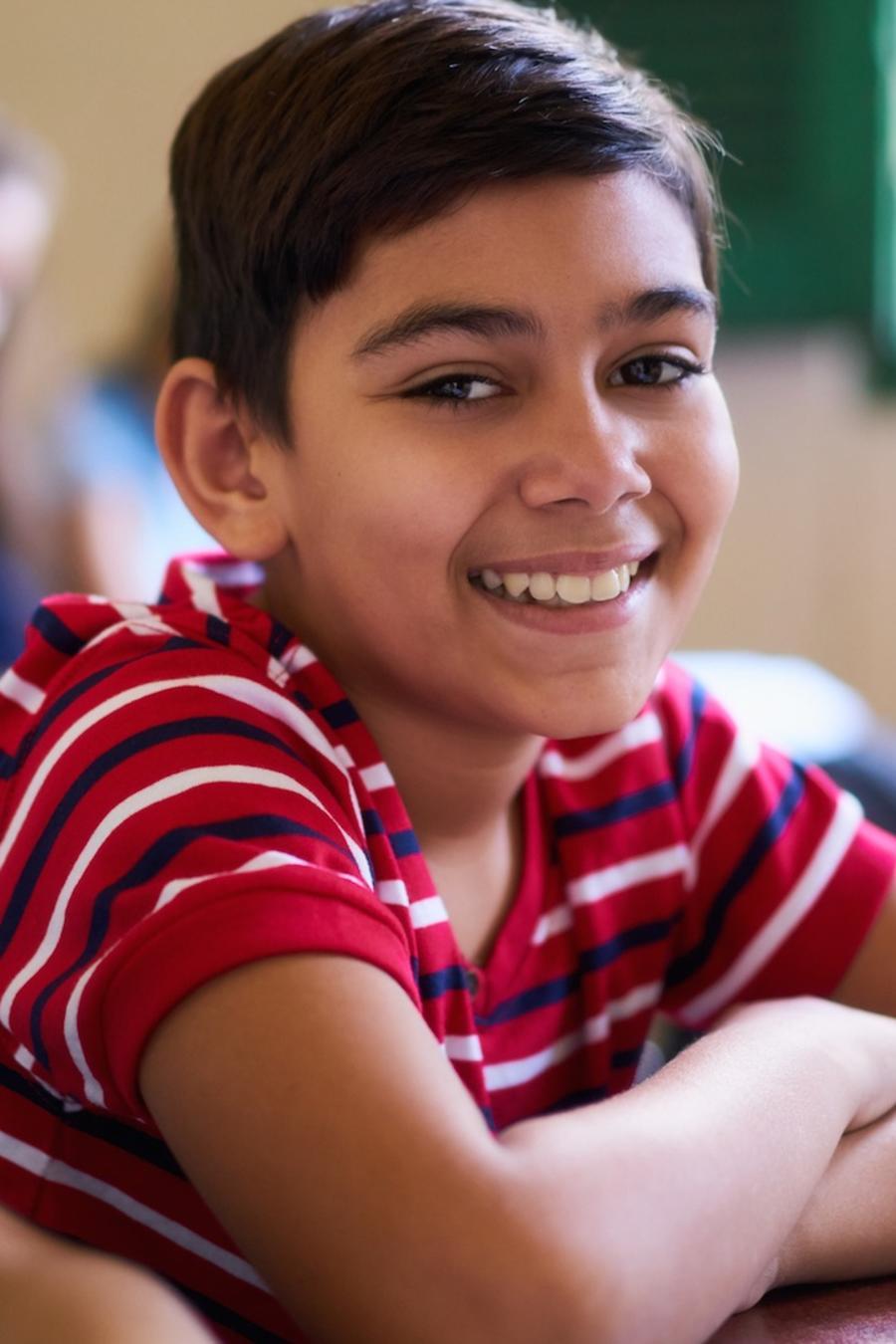 Niño sentado en aula de escuela